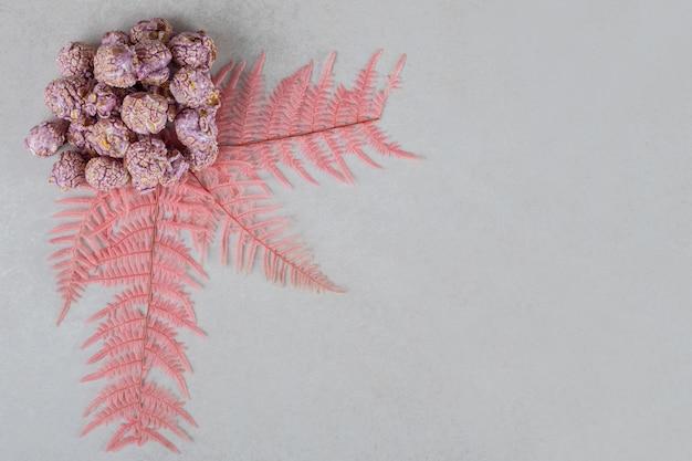 Feuilles décoratives ornant un petit tas de bonbons de maïs soufflé sur une table en marbre.