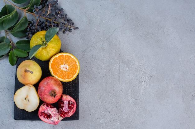 Feuilles décoratives avec des poires, des grenades et des mandarines entières et tranchées sur un tableau noir sur fond de marbre.