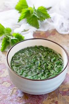 Les feuilles écrasées brassaient des orties crues sur la table de la cuisine sur un fond rustique.