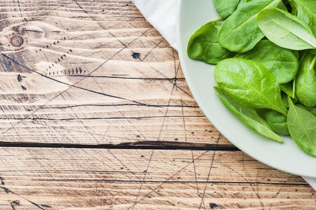 Feuilles d'épinards frais dans un bol sur la table en bois rustique. espace de copie