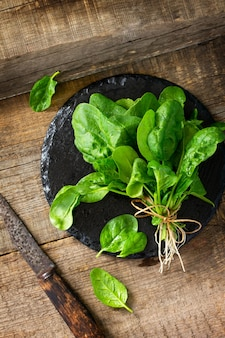 Feuilles d'épinards à salade fraîche sur la table de cuisine en bois espace libre pour votre texte vue de dessus