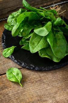 Feuilles d'épinards à salade fraîche sur la table de cuisine en bois espace libre pour votre texte
