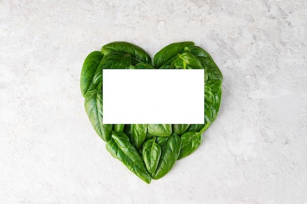 Les feuilles d'épinards sont disposées en forme de cœur, avec une place pour l'inscription.