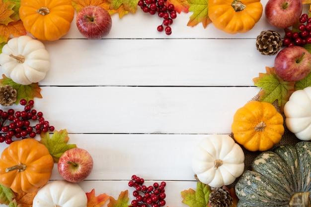 Feuilles d'érable automne avec baies citrouille et rouge sur bois blanc. concept de jour de thanksgiving