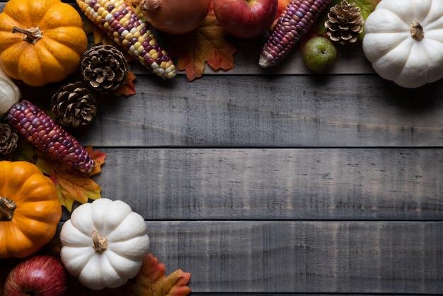 Feuilles d'érable automne avec baies citrouille et rouge sur fond en bois. thanksgiving concep