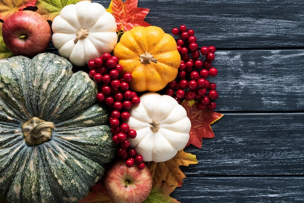 Feuilles d'érable automne avec baies citrouille et rouge sur vieux bois. concept de jour de thanksgiving.