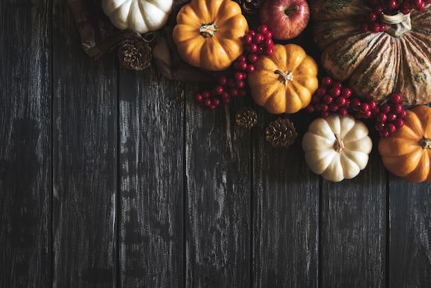 Feuilles d'érable automne avec baies citrouille et rouge sur vieux bois. concept de thanksgiving.