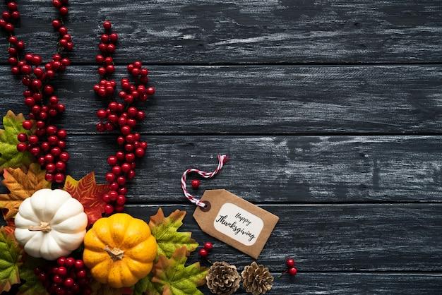 Feuilles d'érable automne avec baies citrouille et rouge sur vieux bois.