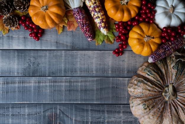 Feuilles d'érable automne avec citrouille, maïs et baies rouges