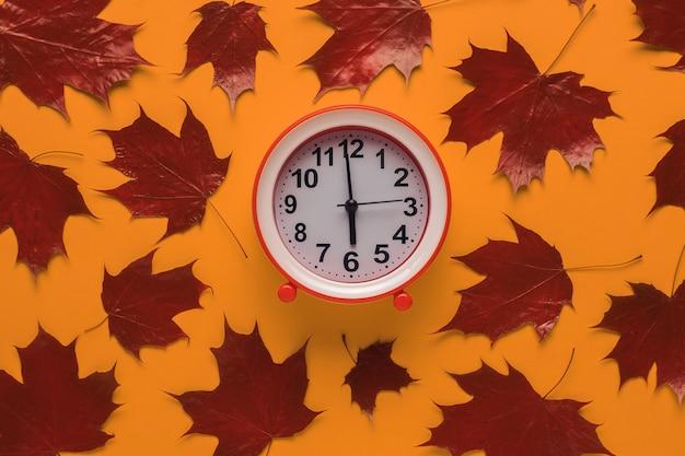 Feuilles d'érable d'automne rouges et un réveil rouge sur fond orange.