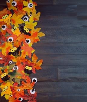 Les feuilles d'érable aux couleurs d'automne et les yeux se trouvent sur un fond marron en bois avec un espace de copie heure d'halloween