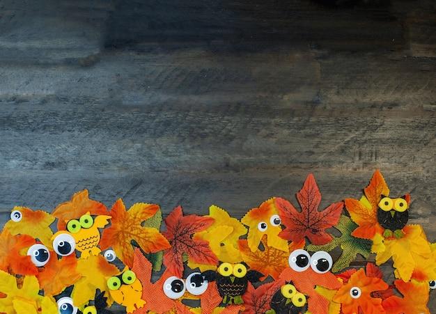 Feuilles d'érable de couleurs d'automne et d'yeux se trouvant sur fond marron en bois avec copie espace halloween tim