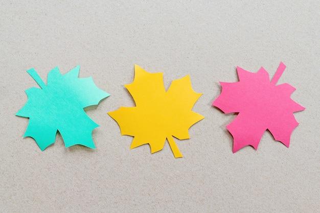 Feuilles d'érable coupées en papier de couleur pour la conception automnale