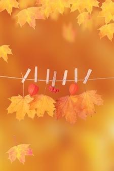 Feuilles d'érable orange d'automne sur fond vertical orange avec espace de copie