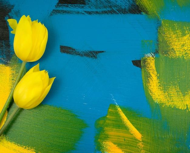 Feuilles d'eucalyptus avec de belles tulipes jaunes à plat sur des œuvres d'art abstraites faites à la main
