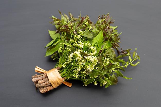 Feuilles et fleurs de neem sur table sombre.
