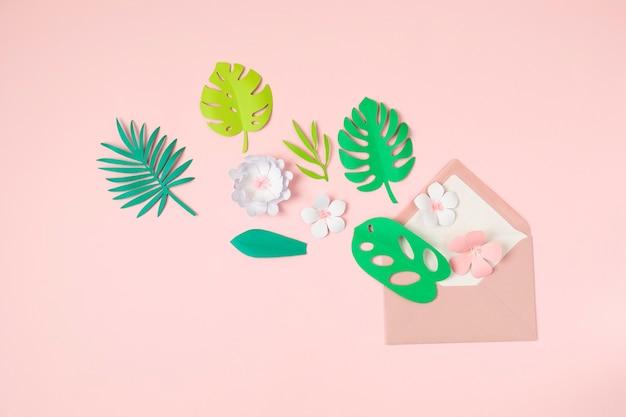 Feuilles et fleurs tropicales en papier sur un mur pastel rose. vacances exotiques d'été, vue de dessus à plat