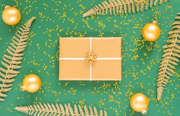 Feuilles de fougère dorées et coffrets cadeaux avec des boules de noël sur fond vert avec des étoiles dorées scintillantes