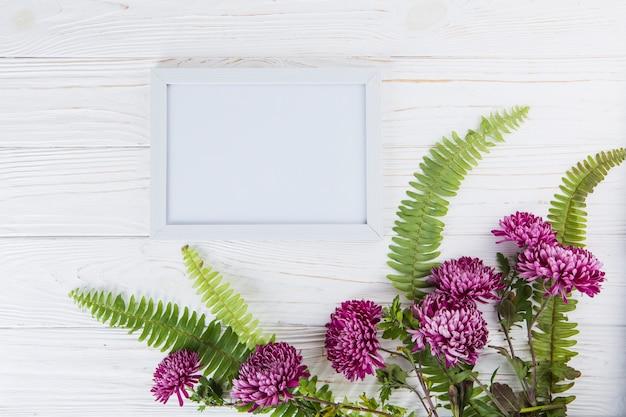 Feuilles de fougère verte à fleurs violettes et cadre sur table