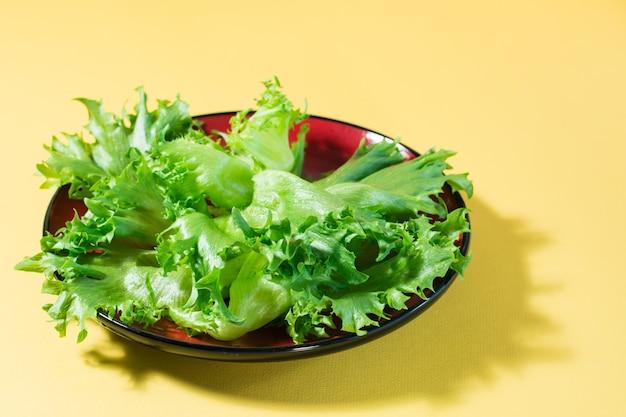 Feuilles fraîches de laitue frisée sur une assiette sur une table jaune.