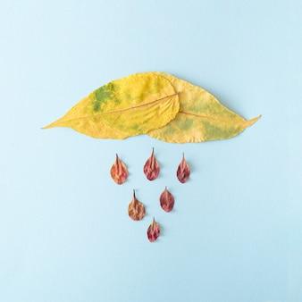 Feuilles jaunes séchées avec plusieurs petites feuilles en dessous sur fond bleu. concept pluvieux d'automne des feuilles et du temps