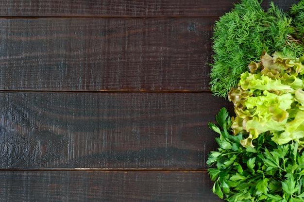 . feuilles de laitue, aneth, persil sur une table en bois sombre. verts frais du jardin. espace libre pour une inscription.