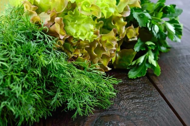 Feuilles de laitue, aneth, persil sur une table en bois sombre. . verts frais du jardin.
