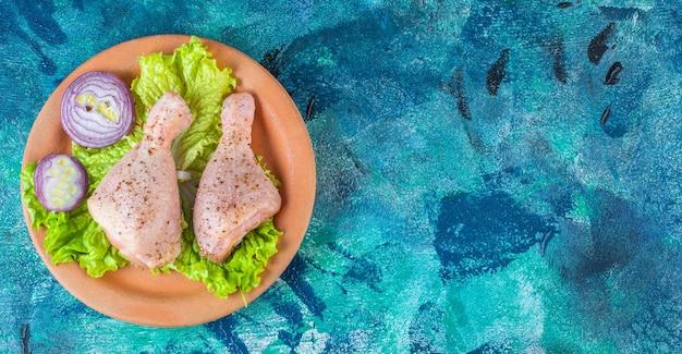 Feuilles de laitue oignon et pilon de poulet sur une plaque d'argile