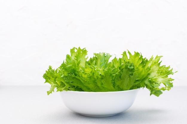 Feuilles de laitue verte fraîche dans un bol sur la table. alimentation équilibrée. copier l'espace