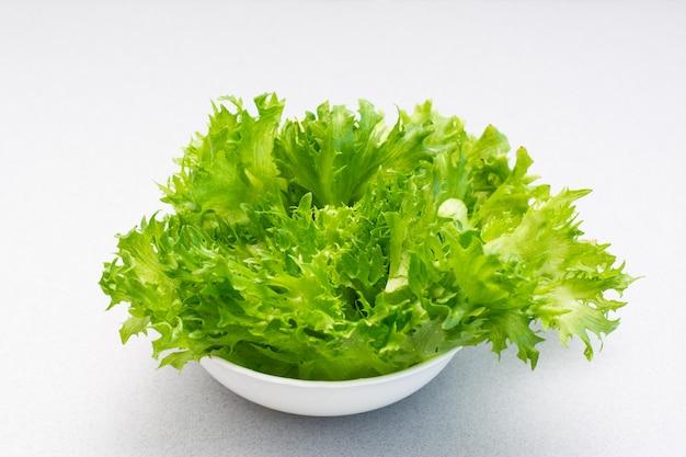 Feuilles de laitue verte fraîche dans un bol sur la table. alimentation équilibrée