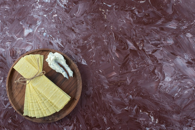 Feuilles de lasagne au yaourt sur une assiette en bois, sur la table en marbre.