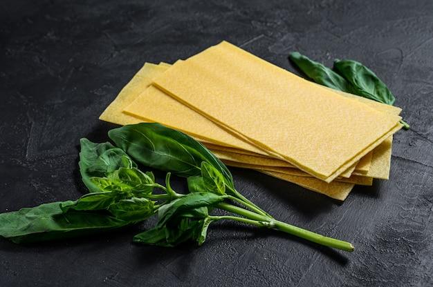 Feuilles de lasagne crues et feuilles de basilic. fond noir. vue de dessus. espace pour le texte