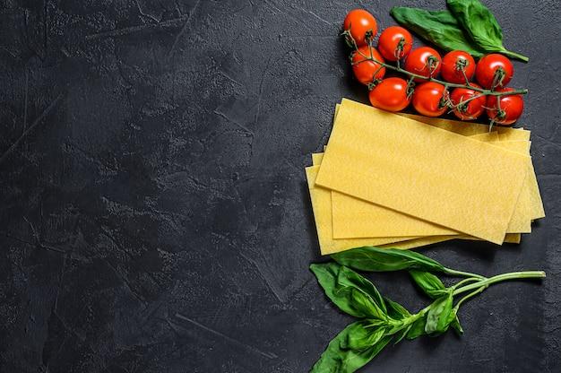 Feuilles de lasagne crues. ingrédients basilic, tomates cerises