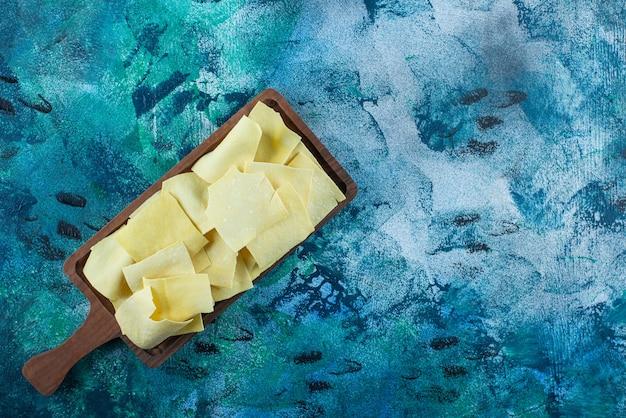 Feuilles de lasagne sur une planche, sur la table bleue.