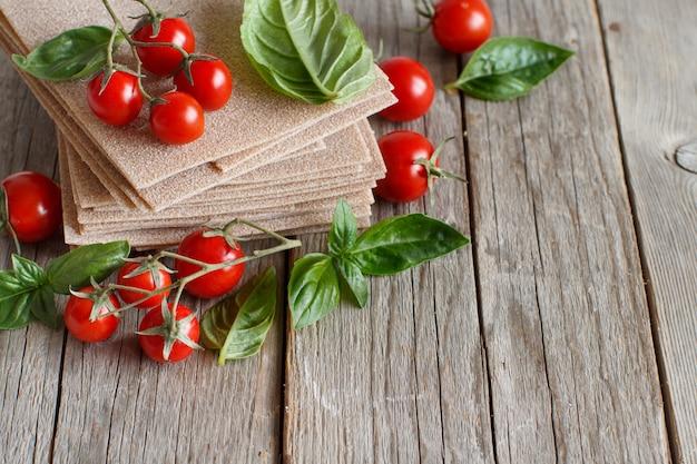 Feuilles de lasagnes crues, basilic et tomates cerises sur une table en bois