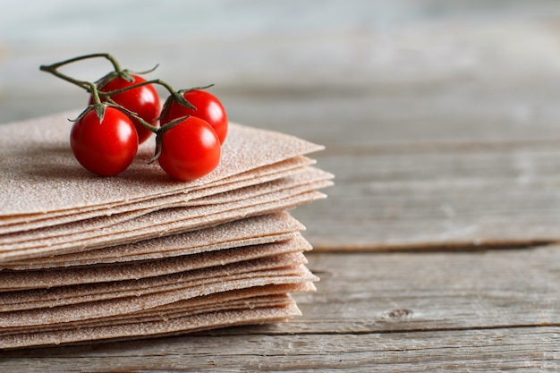 Feuilles de lasagnes crues et tomates cerises sur une table en bois se bouchent