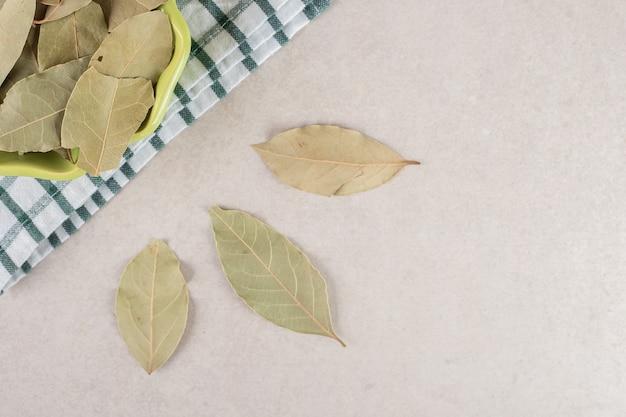 Feuilles de laurier séchées vertes dans un bol en céramique.