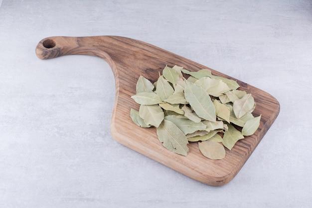 Feuilles de laurier sèches sur un plateau en bois. photo de haute qualité