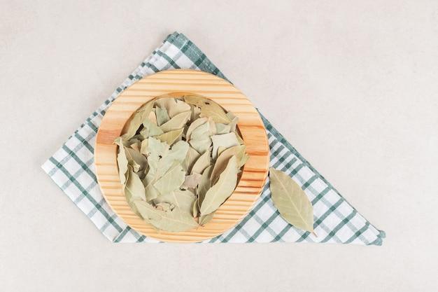 Feuilles de laurier vert frites sur un plateau rustique en bois.