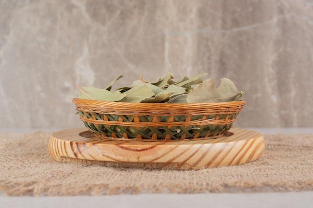Feuilles de laurier vert séchées sur un plateau en bois.