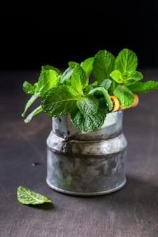 Feuilles de menthe, bouquet frais de menthe dans un vieux vase seau rustique sur un vieux fond sombre