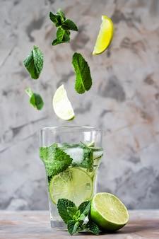 Les feuilles de menthe et de citron vert volent dans un verre avec du mojito avec de la glace sur un fond gris