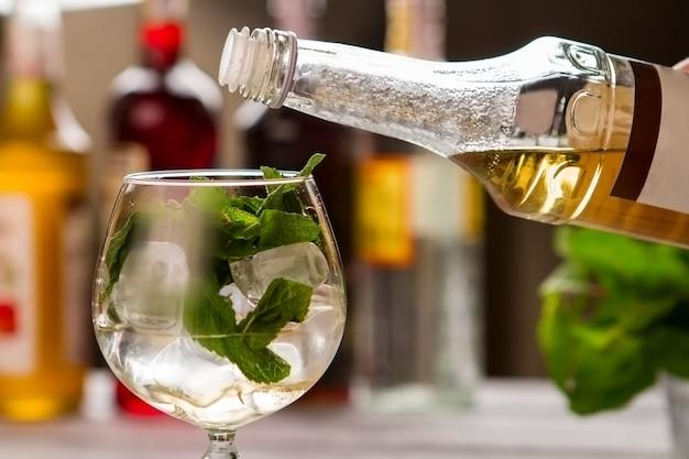 Feuilles de menthe dans un verre à vin. bouteille avec liquide jaune. sirop de fleur de sureau pour cocktail hugo. préparation de boisson au bar.