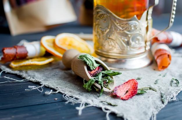 Feuilles de menthe thé vert à la fraise dans une cuillère en bois, tranche de citron