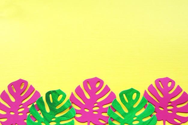 Feuilles de monstera en papier rose et vert sur un fond de papier jaune.