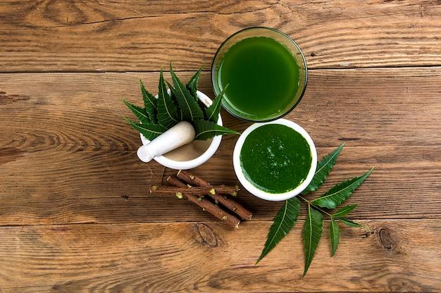 Feuilles de neem médicinales dans le mortier et pilon avec pâte de neem, jus et brindilles sur bois