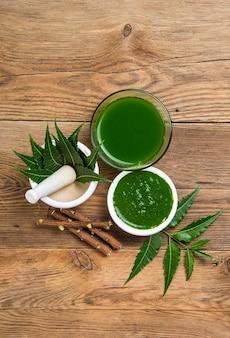 Feuilles de neem médicinales dans un mortier et un pilon avec de la pâte de neem
