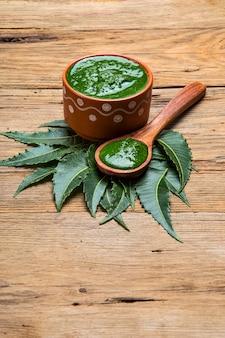 Feuilles de neem médicinales avec pâte sur bois