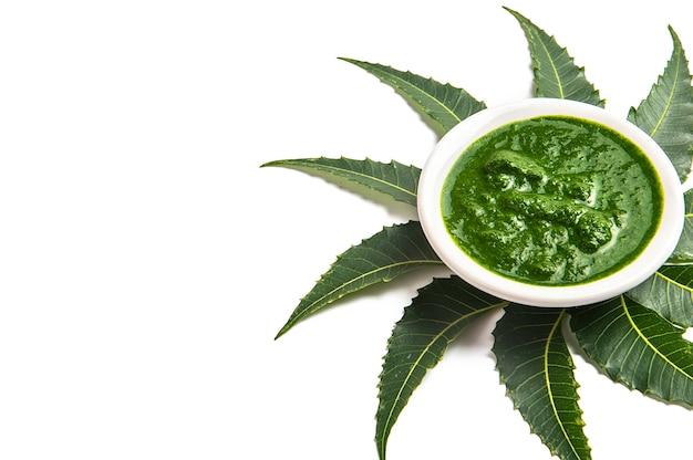 Feuilles de neem médicinales avec pâte dans un bol sur blanc.