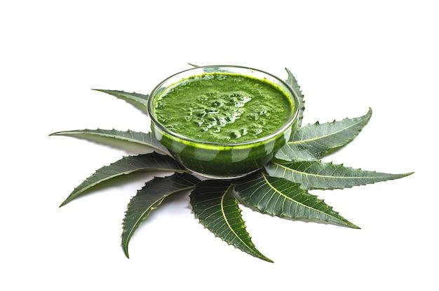 Feuilles de neem médicinales avec de la pâte dans un bol sur une surface blanche.